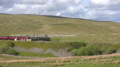 A steam train passes along a hillside in the English countryside. Stock Footage