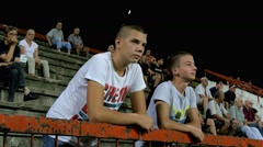 Two young boys watching football or soccer game on the stands, close up, 4K Stock Footage