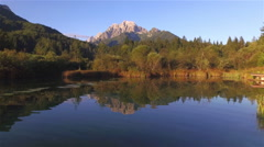 AERIAL: Flying over beautiful lake towards the big mountains Stock Footage