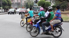 People on the motor scooter riding on the city in Thailand Stock Footage