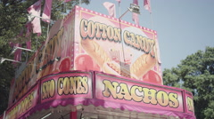 A carnival cart that sells cotton candy, corn dogs, sno cones and nachos Stock Footage