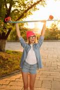 Overjoyed girl holding skateboard Stock Photos