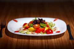 Fresh salad on table with folk and knife Stock Photos