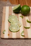 Fresh green lime with slices on wooden bamboo kitchen board closeup Stock Photos