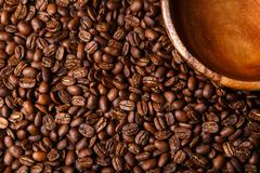 Brown coffee beans background with wooden dish closeup Stock Photos