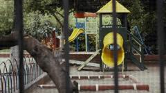 4k establishing shot empty urban public playground behind fence/wire - stock footage