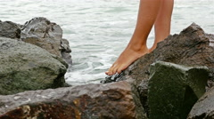 Bare female legs passing on rocky sea shore Stock Footage
