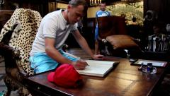 Man writes in a guest book in a luxury house Stock Footage