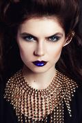 Closeup portrait with deep blue eye, creative makeup and golden accessories Stock Photos