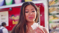 A young woman offers cotton candy to the camera - stock footage