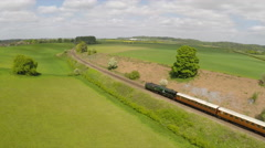 An aerial of a steam train as it passes through the English countryside at high Stock Footage