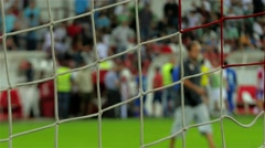 Goal net in focus, football or soccer players leaving field and fans on stadium. Stock Footage