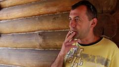 Man smoking a cigarette near the house Stock Footage