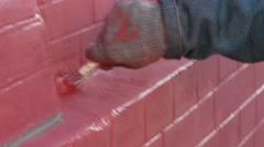 Person painting a red brick wall with brush Stock Footage
