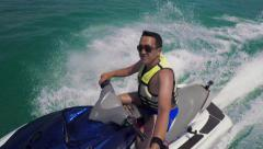 Young Asian male rides jet ski on sea and holds a selfie stick Stock Footage