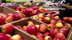Woman selecting gala apple in grocery store - stock footage