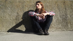 Man long haired sitting alone sad on grunge wall 4K Stock Footage