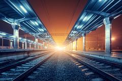 Railway station at night. Train platform in fog. Railroad - stock photo