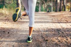 Runner feet running on road close-up on shoe. woman fitness - stock photo