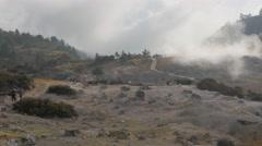 Tourists walk towards Kawah Sikidang volcanic crater,Dieng,Java,Indonesia Stock Footage