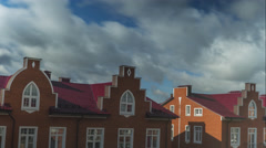 Smooth time lapse of clouds flying over red brick town houses Stock Footage