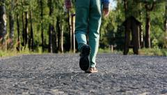 Boy walking along the road from a stone blocks on nature Stock Footage