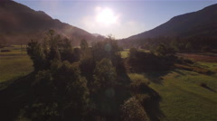 AERIAL: Flying above treetops in beautiful misty mountain valley - stock footage