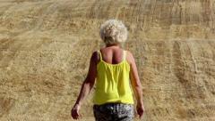 Woman walking on a mown field Stock Footage