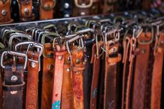 Stock Photo of Hand crafted leather belts with unique buckles on market in Mexico