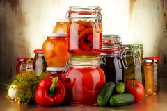 Jars with pickled vegetables and fruity compotes. Preserved food - stock photo