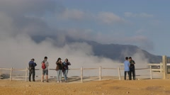 Tourists make selfies at Kawah Sikidang volcanic crater,Dieng,Java,Indonesia Stock Footage