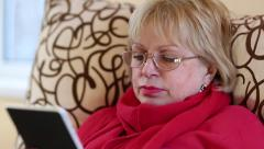 Senior woman sitting on a sofa and using electronic book. Woman with e-book Stock Footage