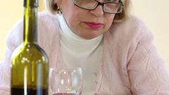 Depressed senior woman with bottle of wine on the table looking at the camera Stock Footage