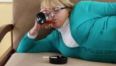 Fat depressed senior woman lying on the couch and drinking brandy Stock Footage