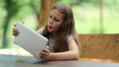 Beautiful girl with tablet computer sits on the bench in summerhouse Stock Footage