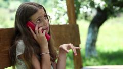 Beautiful girl with smartphone sits on the bench in summerhouse Stock Footage