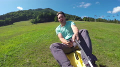 Smiling man riding the roller coaster summer sledge in nature - stock footage