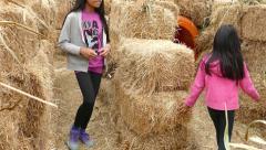 Two Girls Walk Through Halloween Hay Stack Maze Stock Footage