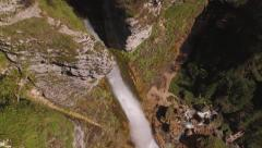 AERIAL: Majestic big waterfall falling down the mountain rocky wall Stock Footage