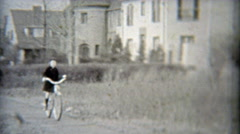 1937: Rich girl riding bike past mansions. Stock Footage