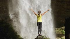 SLOW MOTION: Young woman raising hands towards the majestic waterfall - stock footage