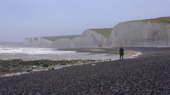 A woman walks along the White Cliffs of Dover near Beachy Head in Southern Stock Footage