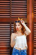 Pin-up girl straightens sunglasses and holding lollipop. - stock photo