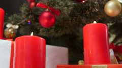 Red candles burning under the festively decorated Christmas tree Stock Footage