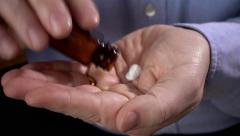 Man shaking pills into hand from bottle Stock Footage