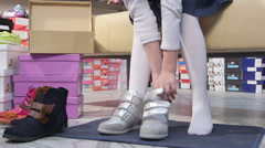Child choosing footwear in childrens shoe store tries on leather velcro sneakers Stock Footage