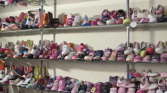 Stock Video Footage of Rows of shelves piled high with new children's footwear in the shoe store