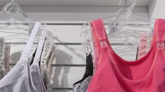 New cotton bras on hangers in lingerie and underwear department - stock footage