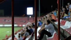 People sitting on stadium stands and watching football or soccer game,iron fence Stock Footage