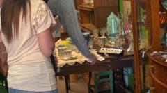 Two friends shopping in an antiques store - stock footage